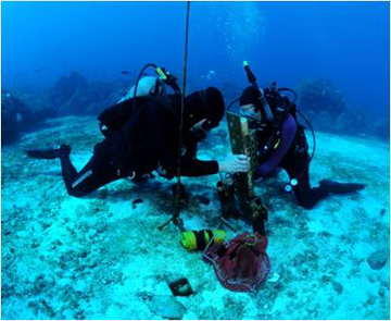 Two divers kneeling on the sea floor, removing an instrument from a rack situated on the seafloor.