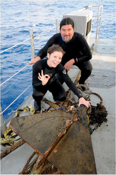 Two researchers standing on a boat deck next to a large anchor hauled up off the reef