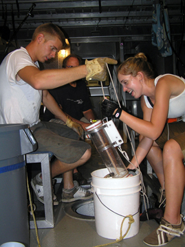 Two researchers hold a water sampling instrument over a white bucket after drawing it up through a small opening in the deck of a boat.