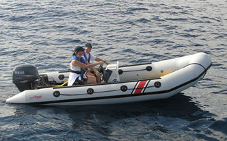 Two people seated in a small rigid hull inflatable boat on the water.