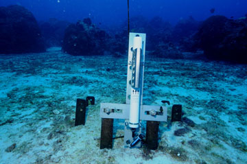 A white, tube-shaped instrument mounted vertically to a cross-shaped bracket attached to a metal rack partially buried in the sand.  Blue water and coral colonies are visible in the background.