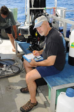 Man sitting on dive bench while writing on a clipboard.