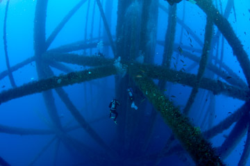 Two divers swim among the underwater crossbeams of an oil and gas production platform.