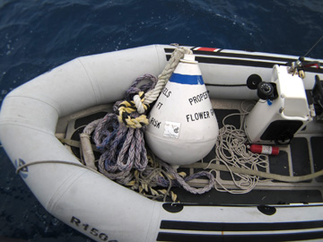 A mooring buoy sitting on the floor of a rigid hull inflatable boat.