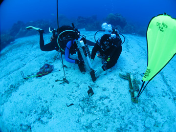 Divers changing out water quality instruments at an underwater station. An inflated lift bag rests on the sand nearby.