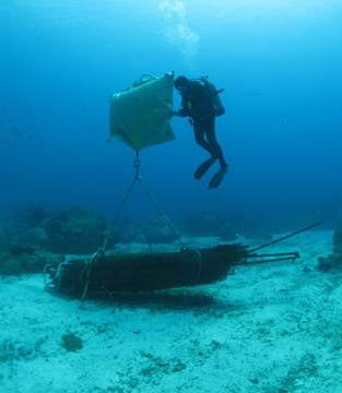 A diver filling a lift bag being used to lift heavy debris off the seafloor.