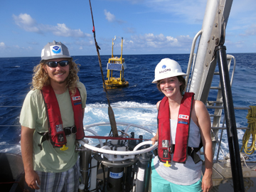 Two students stand on either side of a CTD carousel on the back deck of R/V MANTA. In the background, a large TABS buoy is floating on the water's surface.