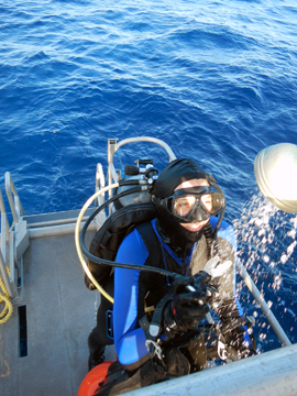 Diver using a shower rinse on the dive platform