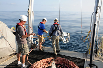 Three people lowering an ROV into the water off the back of a boat.