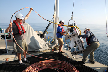 Three men pull an ROV back onto the deck of a boat.