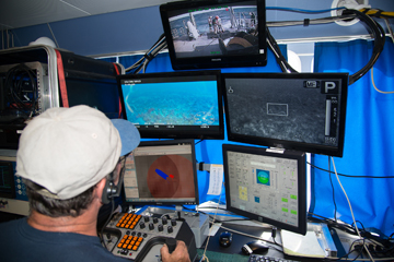 ROV pilot seated in front of a bank of display monitors