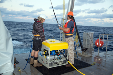 Two people in hardhats ready the ROV for launch and prepare to attach the lift cable.