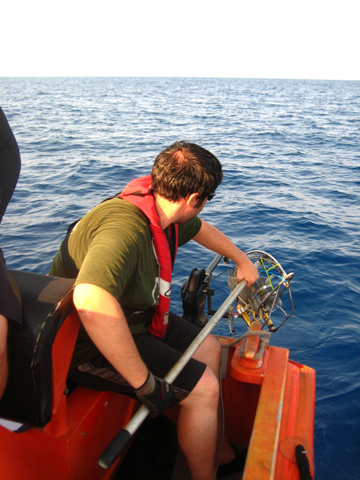A researcher about to lower a drop camera setup over the side of a small boat.