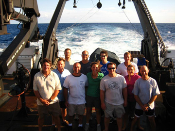 Group photo of the members of the science team standing on the back deck of a ship.
