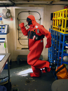 "Man in bright orange ""gumby"" survival suit during a drill on board a ship."