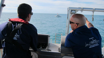 Two men standing at the stern control station of the R/V Manta.