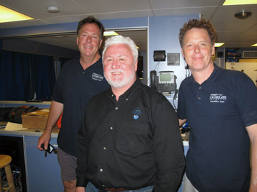 Three men standing in the dry lab of R/V Manta.
