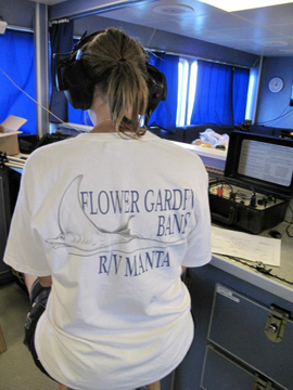 A woman wearing headphones while sitting on a stool with her back to the camera. The back of her shirt says Flower Garden Banks R/V Manta.