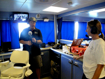 Two people standing in the dry lab of R/V Manta adjusting equipment.