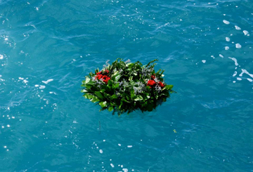 Memorial wreath of greens floating on the water.