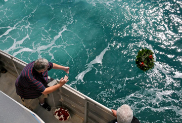 Three people along a boat rail tossing a wreath into the sea.
