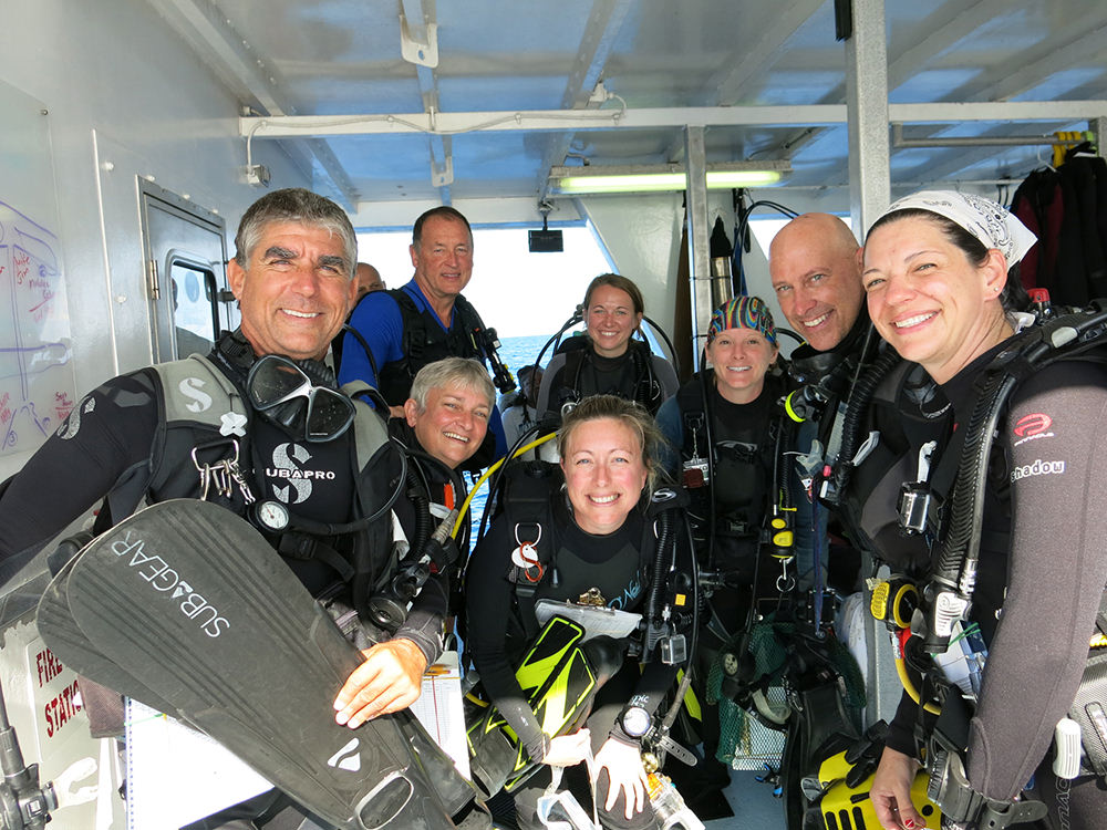 A group of 8 divers in scuba gear ready to make a dive