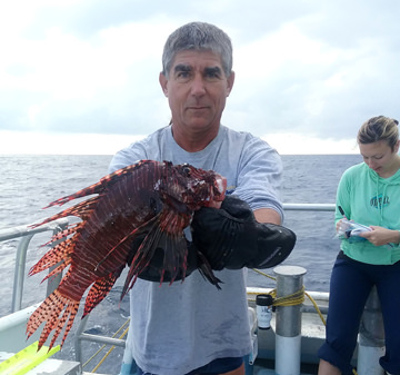 Man holding up large lionfish