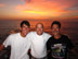 Three men standing together in front of an orange sunset.