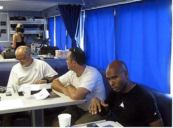 Three men sitting around a table in the galley of the R/V Manta.