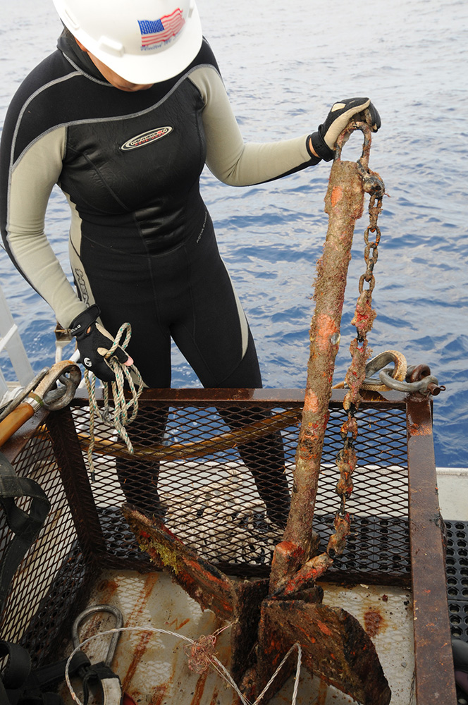 A female diver in a wetsuit and wearing a hardhat standing on the back deck of a boat next to a hoisting cage containing a large anchor recently retrieved from the bottom of the ocean.