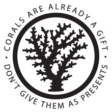 Silhouette of a branching coral enclosed in a black circle. Around the circle it says Corals Are Already a Gift, Don't Give them as Presents.