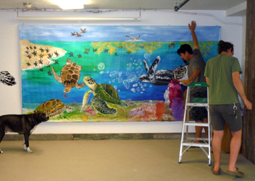 Two men hanging a large sea turtle mural on a wall as a dog watches.