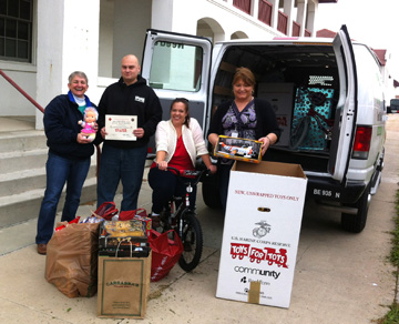 Four people posing with toys collected and ready to be loaded into a van for Toys for Tots