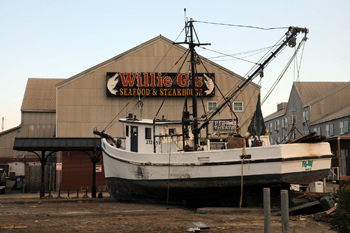 Shrimp boat standing upright in the parking lot of a restaurant on the bay side of Galveston Island.