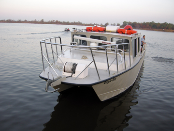 A 48 foot catamaran style boat floating in the water with bow foward.