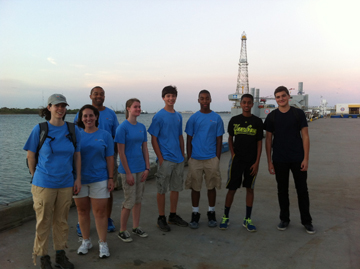 Group of people standing on a pier in Galveston with an oil rig derrick visible behind them.