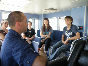Several students talking to NOAA Corps officer on boat