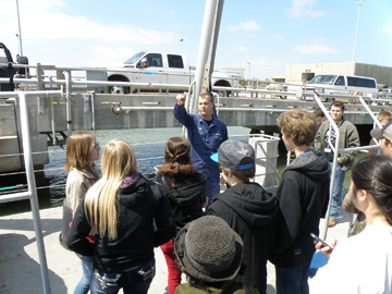 Jamie talking to a group of students on the back deck of the MANTA