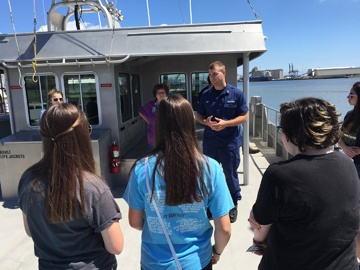 Students listening to LTJG Jamie Park on the top deck of R/V MANTA