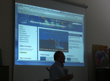 GP silhouetted in front of a screen showing information about the National Marine Sanctuary Foundation