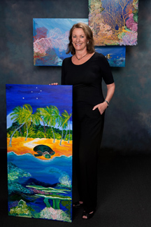 Woman standing amid three of her paintings