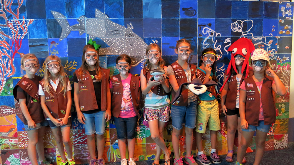 A group of girls in Brownie uniforms wearing paper scuba masks and standing in front of a coral reef mural