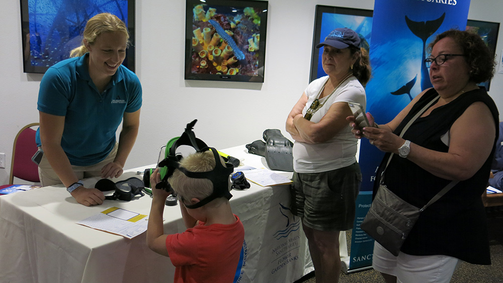 A woman from Moody Gardens helping a young boy try on a full face dive mask as two women watch nearby.