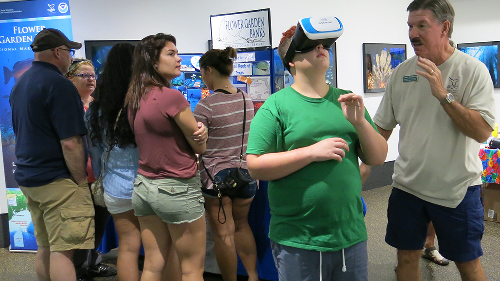 A boy wearing virtual reality goggles to view the sanctuary as a volunteer stands by to assist.