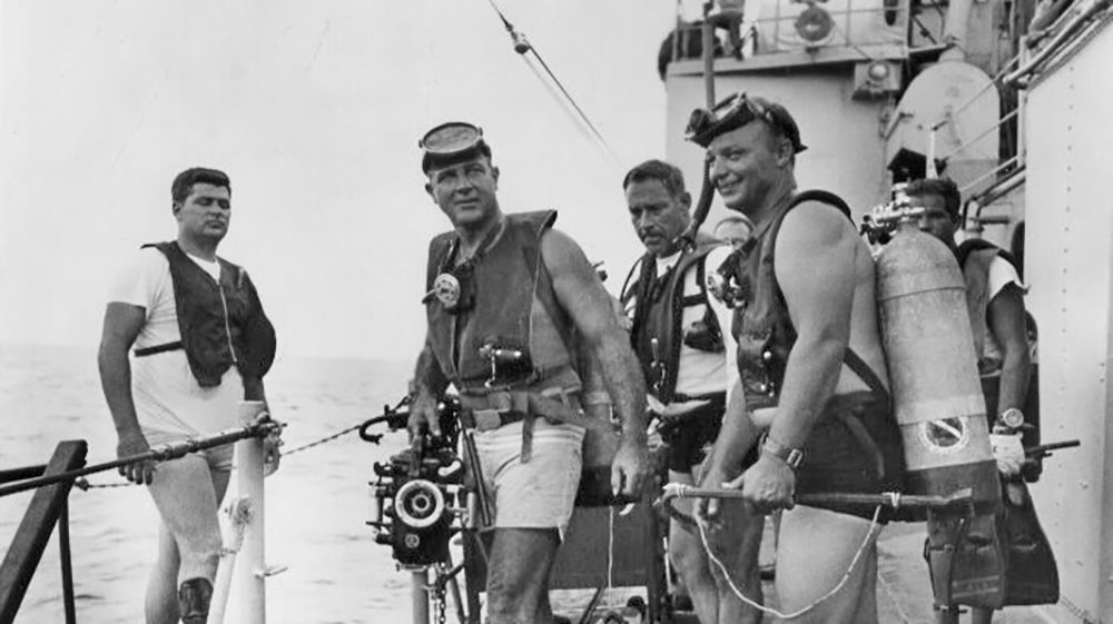 Black and white photo of scuba divers on the deck of a Navy ship in 1967