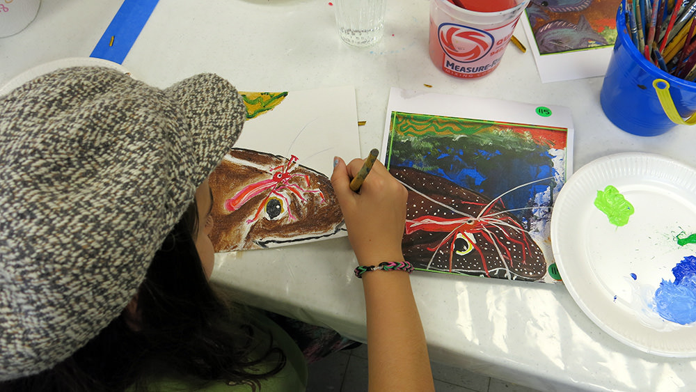 A child painting a picture of an eel with a shrimp sitting on its head