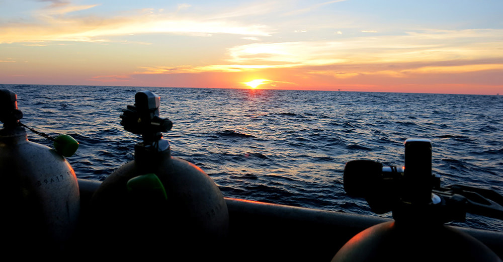 Sunset over the water with the tops of some scuba tanks in the foreground