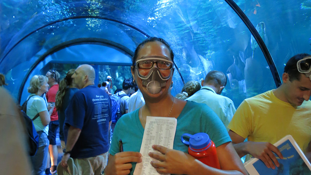 A woman wearing a paper scuba mask over her face while standing in a tunnel through an aquarium with a bunch of other adults. A man to her right has a paper scuba mask pushed up on his forehead.