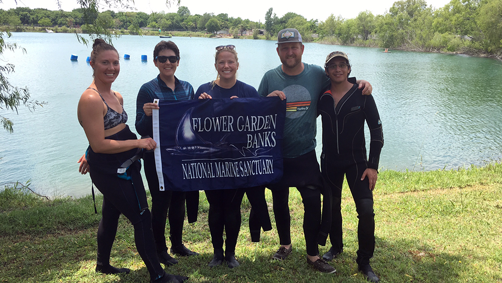 Five divers standing by a lake with a Flower Garden Banks National Marine Sanctuary banner