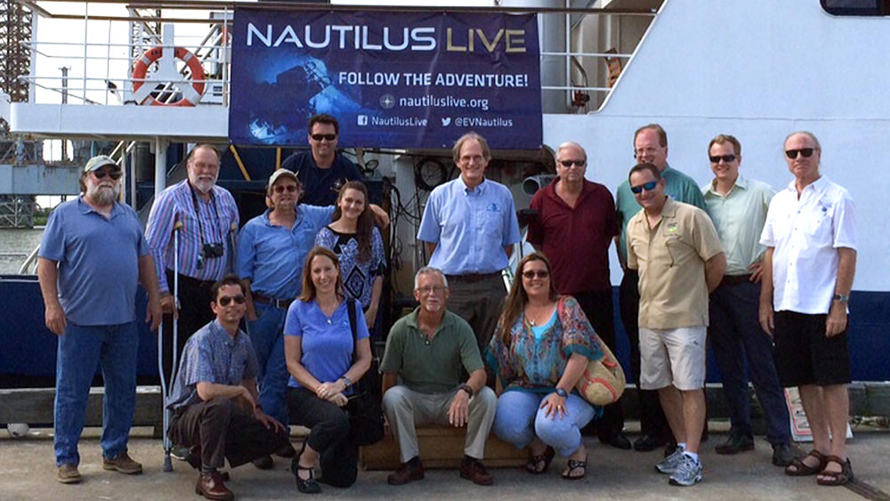Council members standing in front E/V NAUTILUS, a ship docked in Galveston